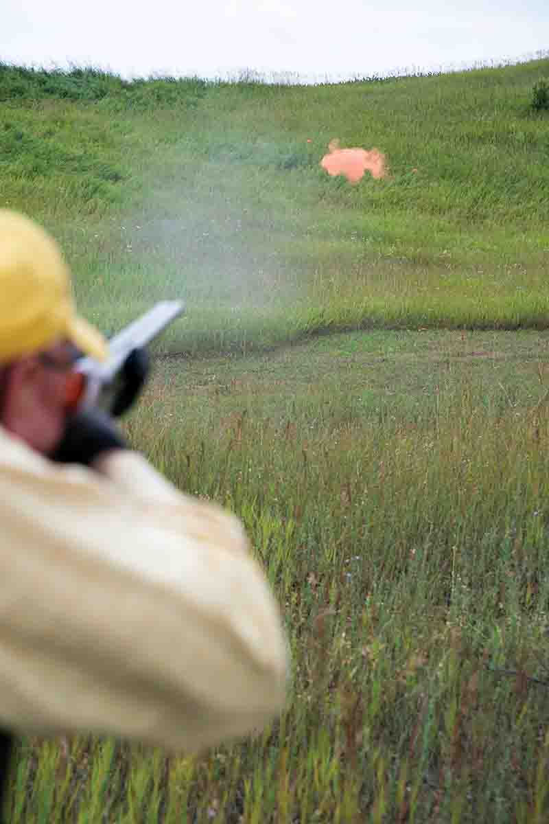 At impact, notice that the muzzle has traveled beyond the edge of the powdered clay target.